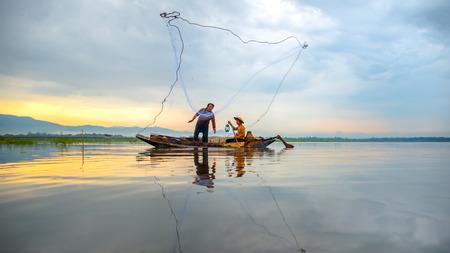 Fisherman of Bangpra Lake in action when fishing in the sunshine morning, Thailand, select focus