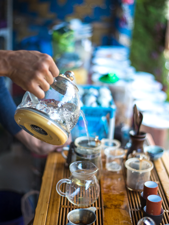 smal: Hand that pours chinese green tea from glass kettle to smal cup, select focus