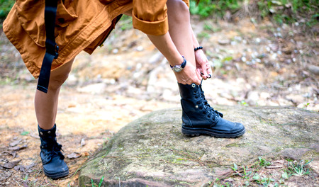 shoelace: Woman hiking tying shoelace on forest trail