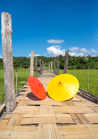 The red and yellow umbrella on the wooden bridge in the green rice field. Mae Hongson Thailand