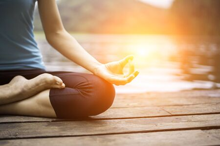 Close up hand. Woman do yoga outdoor. Woman exercising yoga at the nature background, select focus