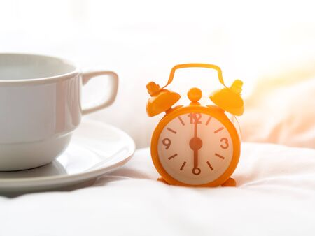 Fresh morning coffee and clock on the bed.