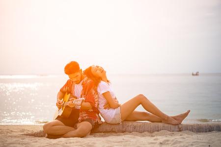 Śliczne gitary latynoska para gry serenadę na plaży w miłości i objąć