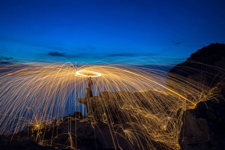 steel wool: Showers of hot glowing sparks from spinning steel wool on the rock and beach