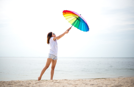 umbella: Young women jumping with umbella and happy on the beach. Travel and Vacation. Freedom Concept