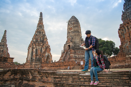 Traveler man and women with backpack walking in temple Ayuttaya ,Thailand