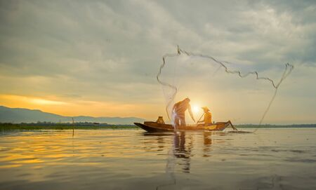 fishermans net: Fisherman of Bangpra Lake in action when fishing, Thailand