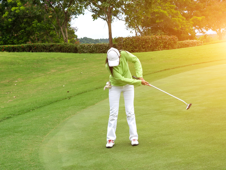 Smiling woman golf player putting successfully ball on green, ball dropping into cup, Stock Photo