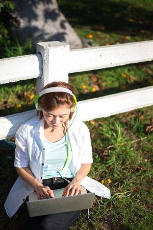 Jonge vrouwen ontspanning het luisteren muziek met notitieboekjezitting op het gras. Buitenshuis. Zonnige dag. Groenetoon 2017