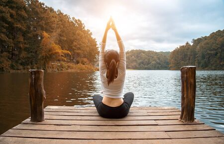 Woman do yoga outdoor. Woman exercising yoga at the nature background, select focus