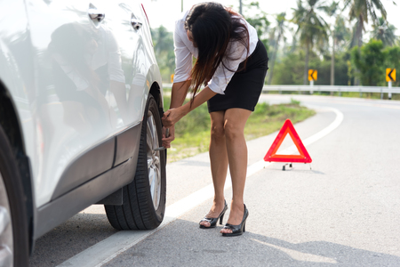 Frustrated business women Driver With Tyre Iron Trying To Change Wheel