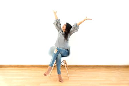 흰색 현대 의자에 앉아 매력적인 아시아 여자 집에서 긴장