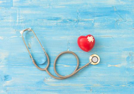 Een enkele alleen rood hart liefde vorm hand oefening bal met pleister MD arts arts stethoscoop blauwe hout achtergrond