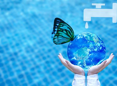 Het drinkwater van de vlinder van blauwe bol op hand. Waterconcept opslaan, element van afbeelding geleverd door NASA Stockfoto