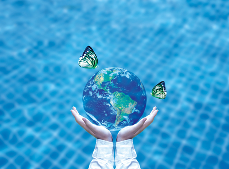 Butterfly drinking water from blue globe on hand.  Saving water concept, Element of image furnished by NASA