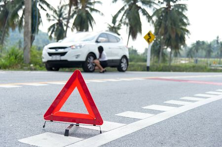 Business woman with a broken car calling for assistance. Focus is on the red triangle sign Stock Photo