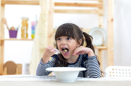 Cute little girl eating cereal with the milk in the kitchen Stock Photo