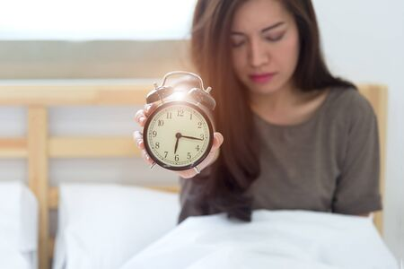 turn table: Young sleeping woman and alarm clock in bedroom at home. focus alarm clock