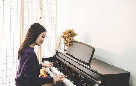 Young pretty beautiful Asian girl sitting at piano Stock Photo