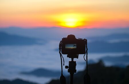 Closeup of a camera on a tripod outdoors. Background Landscape out of focus Stock Photo