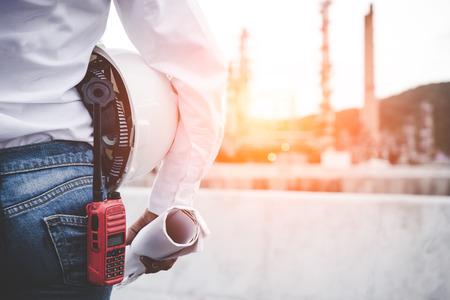 Mujer ingeniero sosteniendo casco blanco y plano con radio para control de seguridad de los trabajadores en la industria de la energía de la planta de energía. Ingeniero Concept Foto de archivo - 81101660