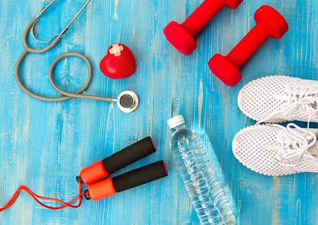 Fitnessapparatuur gymnastiektraining en zoet water met hart en medische stethoscoop op de blauwe achtergrond. Gezond concept. Stockfoto