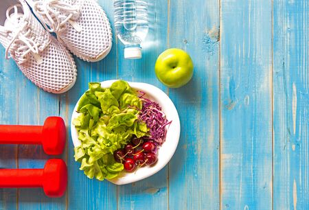 Healthy lifestyle sport equipment fitness, sneakers, green apple, fresh water and healthy food on blue wood background.  Healthy Concept.