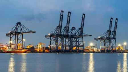 unloading: Container Cargo freight ship with working crane bridge in shipyard at dusk for Logistic Import Export background.  Industry Concept