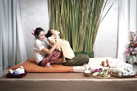 Thai Masseuse doing massage for woman in spa salon. Asian beautiful woman getting thai herbal massage compress massage in spa.She is very relaxed.  Healthy Concept Stock Photo - 82321045