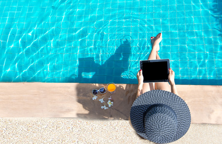 Women lifestyle relaxing near luxury swimming pool sunbath, summer day at the beach resort in the hotel. Summer Concept