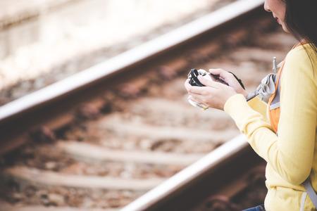 旅行者や観光アジア若い女性地図とカメラを保持しているバックパックを身に着けている電車を待っています。 旅行の概念。