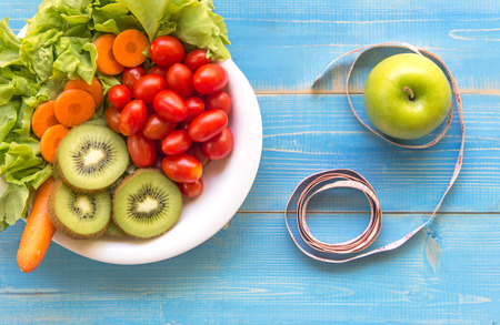 Healthy lifestyle for women diet with measuring tape, vegetable fresh, green apples blue on wooden.  Healthy Concept. Stock Photo
