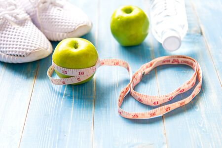 table top: Diet and weight loss with measuring tap, green apple, water and sneakers for fitness on blue wooden background top view.  Healthy Concept.