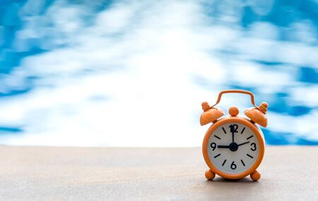 Retro alarm clock on table near swimming pool
