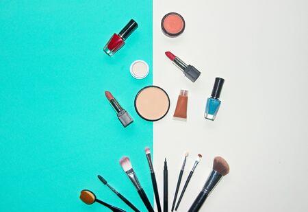 Cosmétiques fond blanc et bleu avec des objets d'artiste maquillage: rouge à lèvres, ombres à paupières, mascara, eye-liner, anticernes, vernis à ongles. Concept de style de vie