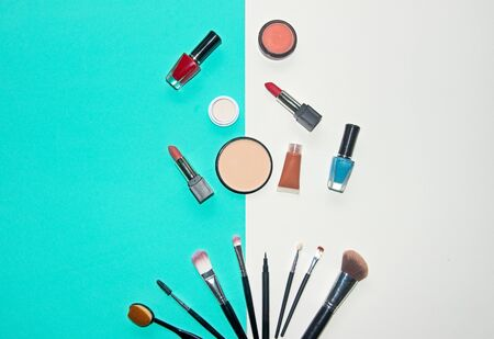 Cosmetics white and blue background with make up artist objects: lipstick, eye shadows, mascara ,eyeliner, concealer, nail polish.  Lifestyle Concept