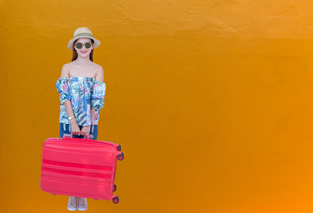 Woman traveler with suitcase on wall color background.  Lifestyle and Travel Concept Stock Photo
