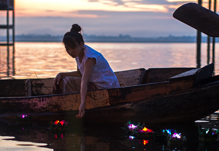 Asian women Loy Kratong Festival on the fishing boat in the reservior, Travel Thailand.