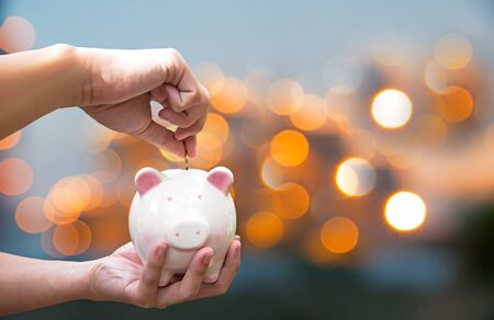 Man holding piggy and putting a coin into piggy bank for future life.  Investment and Saving Concept.