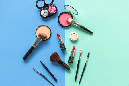 Set cosmetics makeup, brush, eye shadow and lipstick, colourful blue and green background.  Lifestyle Concept Banco de Imagens