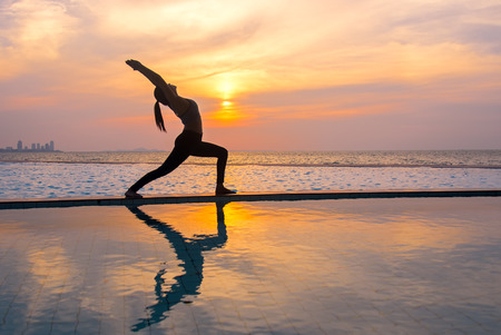 Silhouette young woman practicing yoga on swimming pool and the beach at sunset.  Healthy Concept. Stock Photo