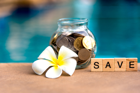 Words of saving money concepts collected in crossword with wooden cubes. Coin full of glass piggy, select focus. Investment Concept.