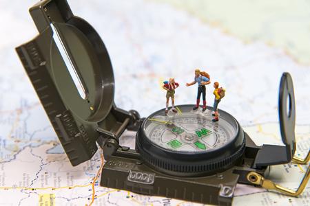 Miniatuurgroepsreiziger met rugzak die zich op woldkaart bevindt voor reis rond de wereld. Reis Concept