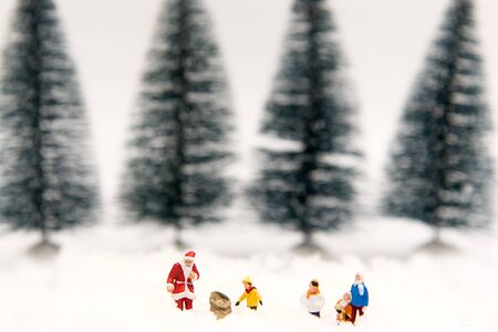 Miniature Santa Claus with Snow man make happy hour for children on Christmas day, Tree background.   Holiday Concept