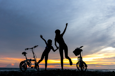 Silhouette freedom biker lovely family at sunset over the ocean.  Sisters bicycling at the beach.  Lifestyle Concept.
