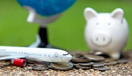 Tourist travel planning for saving money in the piggy for travel airplane with around the world.  Travel  and Saving Concept, select focus Stock Photo