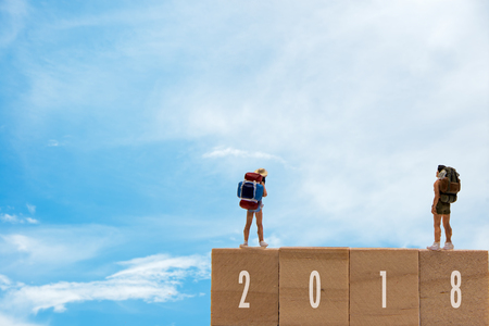 Miniature group traveler standing on wooden 2018 with  new year, blue sky background.  Holiday Concept