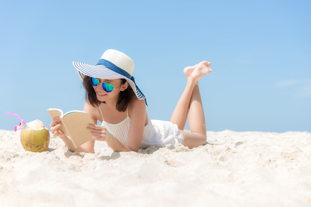 Lifestyle young asian woman relax and reading a book at the beautiful beach on holiday summer, blue sky background.  Summer Concept.