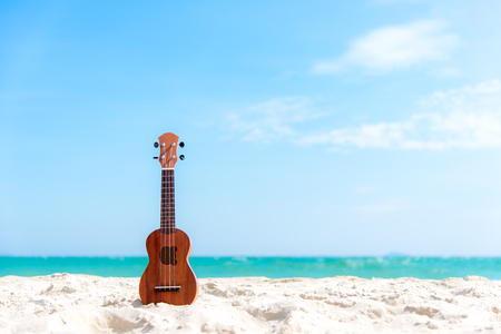 The Summer day with Guitar ukulele for relax on the beautiful beach and blue sky background,copy space. Travel and Summer Concept