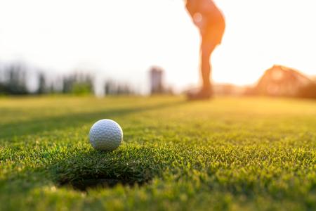 Mujer asiática del golfista que pone la pelota de golf en el golf verde el tiempo determinado de la tarde del sol, foco selecto. Concepto saludable y estilo de vida.